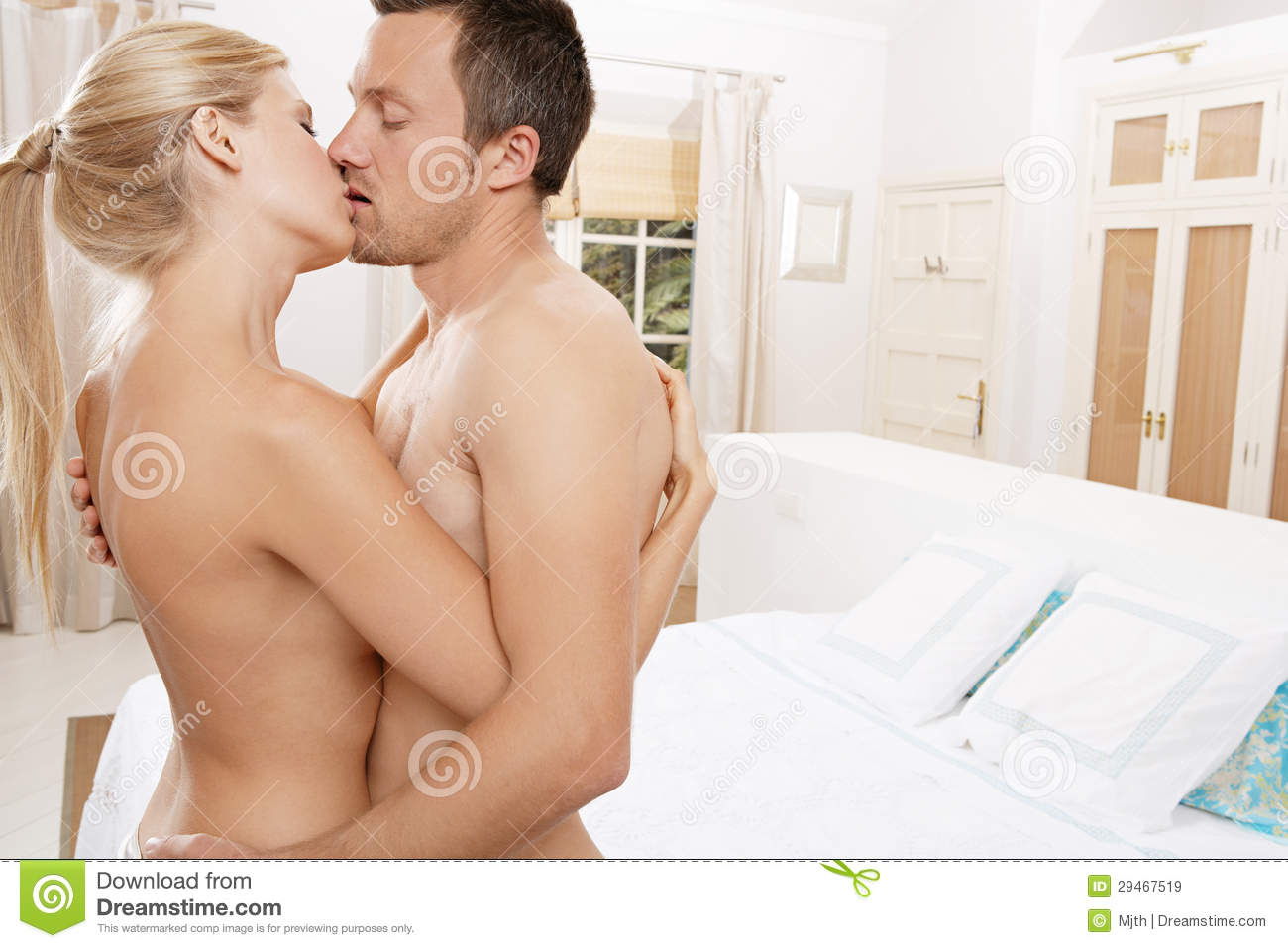 Nude couple hugging and kissing